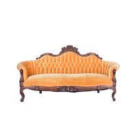 Golden yellow/orange Victorian sofa with ornate wood trim.