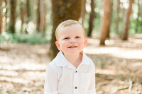 little boy smiling in in the woods