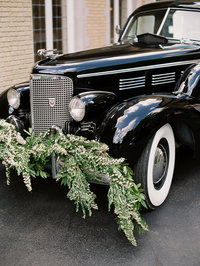 black luxury car sits in front of pinecroft mansion in cincinnati ohio with spirea garland on the front bumper by cincinnati wedding florist roots floral design