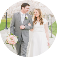 Bride and groom walk through cherry blossom trees at the Utah State Capitol