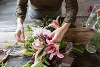 Nashville wedding florist arranging a bouquet with pink lilies