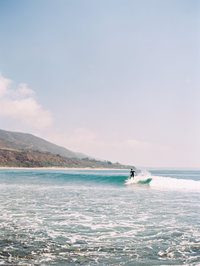 A photograph of a man surfing at Leo Carrilo beach in Malibu, CA