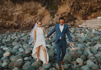 bride and groom walking over rocks