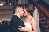 A handsome groom and his beautiful bride embrace holding each other close.