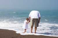 Father holding daughters hand in ocean