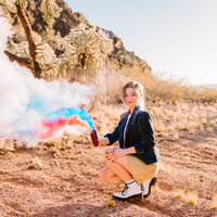 high school senior girl wearing blazer holding two smoke bombs in field