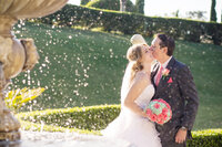 A bride and groom share a kiss in front of a fountain at their Grand Island Mansion Wedding.