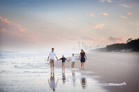 Natural light outdoor portrait of family holding hands on beach at The Gold Coast