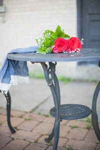 metal table with red  roses sitting on top wrapped with a scarf