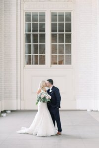 bride and groom kissing on their wedding day at union station dallas venue by catie ann photography