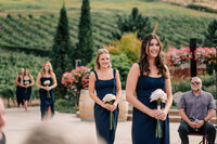 Bridesmaids in navy dresses walking down the aisle during Lake Chelan wedding ceremony at Karma Vineyards