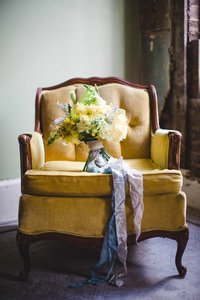 A bouquet sits on a yellow arm chair.