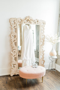 Wedding dress hanging on gold gilded mirror