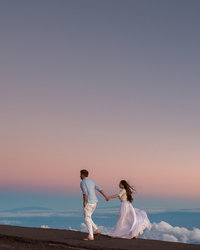 couple walks above the clouds for their sunset honeymoon photo shoot on maui.