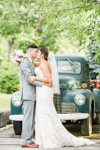 The bride and groom kissing in front of the green truck at Rivercrest Farm photographed by akron ohio wedding photographer