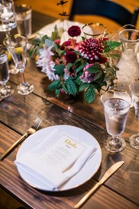 Wedding reception with farm tables and burgundy flowers