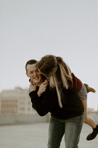 Man holding his fiance on his back and smiling