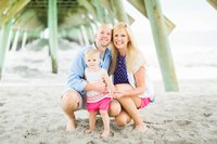 mom, dad, and toddler smiling on beach under pier