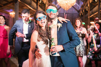 Bride and groom wear fun glasses at reception