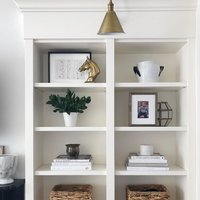 open white shelving beautifully styled with accessories and gold library sconce