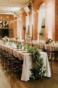 Wedding reception with neutral linens and airy green garlands