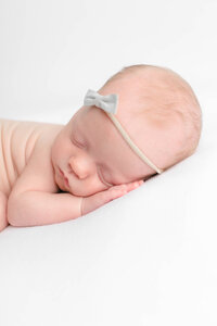 light-skinned baby girl with simple bow on white backdrop sleeping for newborn portraits