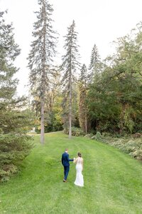 Newlyweds walking down a hill holding hands on the beautiful grounds of Windermere Manor