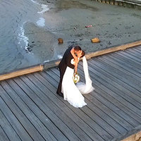 Drone shot of bride and groom kissing on beach