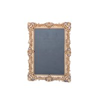 Large ornate gold frame with chalkboard inside.