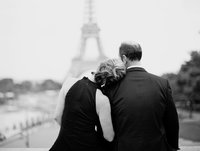 wife lays head on husband's shoulder in front of Eiffel Tower