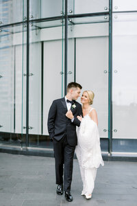 Groom and bride walking in front of the Trump International Tower in Chicago