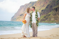 Kissing wedding couple against the NaPali coast of Kauai, Hawaii