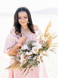 Kiamarie Stone holds bouquet in pink dress and looks down