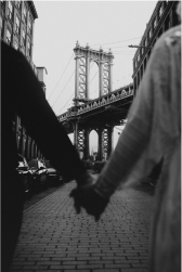 engaged couple holds hands in front of manhattan bridge in dumbo