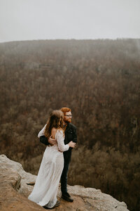 eloping couple standing on a cliff