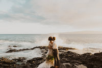 man & woman kissing on rocks