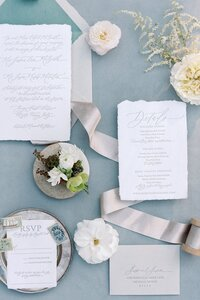 blue and grey invitation suite flat lay with flowers and ribbon by dallas wedding photographer catie ann photography
