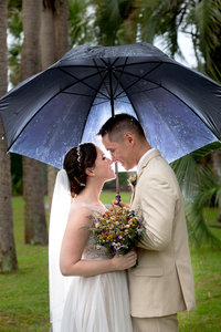 couple smile under an umbrella at their Atalaya Castle wedding