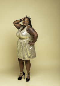 Curvy Black woman in gold dress and black heels