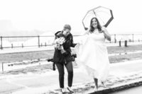 Photographer walking with bride in the rain