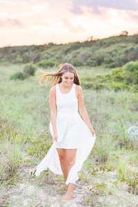 senior in white dressing smiling for portraits at Huntington Beach State Park