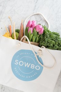 white tote bag with produce and flowers on a marble table