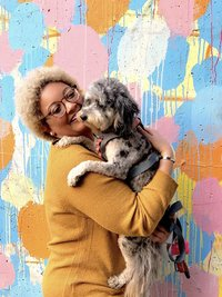 Janelle smiling with & her dog Mila in front of colorful wall in Atlanta