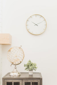 rose gold clock and world globe  in a bright space in a room