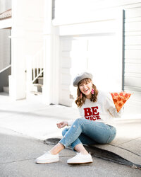 LA photographer holding a slice of pepperoni pizza