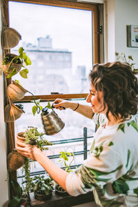 Maria tends to her hanging potted plants hanging in her apartment window