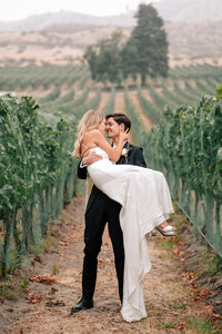 Groom holding bride in the vineyard at Tsillan Cellars winery in Chelan, WA
