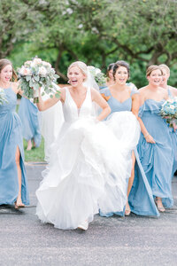 Bride and Bridesmaids run to escape the rain as a thunderstorm rolls in during their wedding party portraits