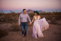 bride with dirty dress and groom holding hands and running in the desert