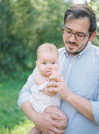 Father holding baby in Maryland family session.